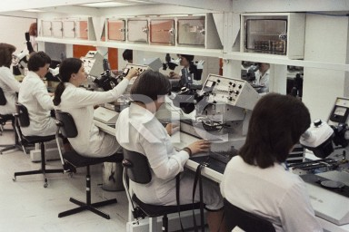 Women at work in white lab coats at Analog Devices 1980